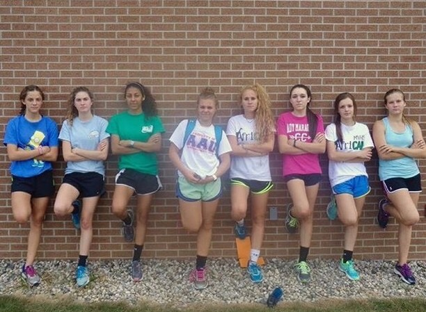Girl Soccer players leaning against a brick wall