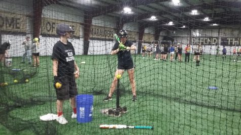 a softball player is in a net, getting ready to swing