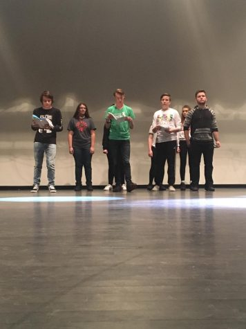 5 students with scripts stand on stage.