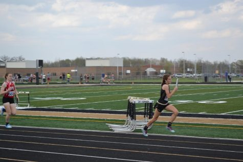 A girl with a baton in her hand runs for first place.