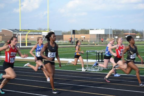 6 girls are running on a track, all racing for first