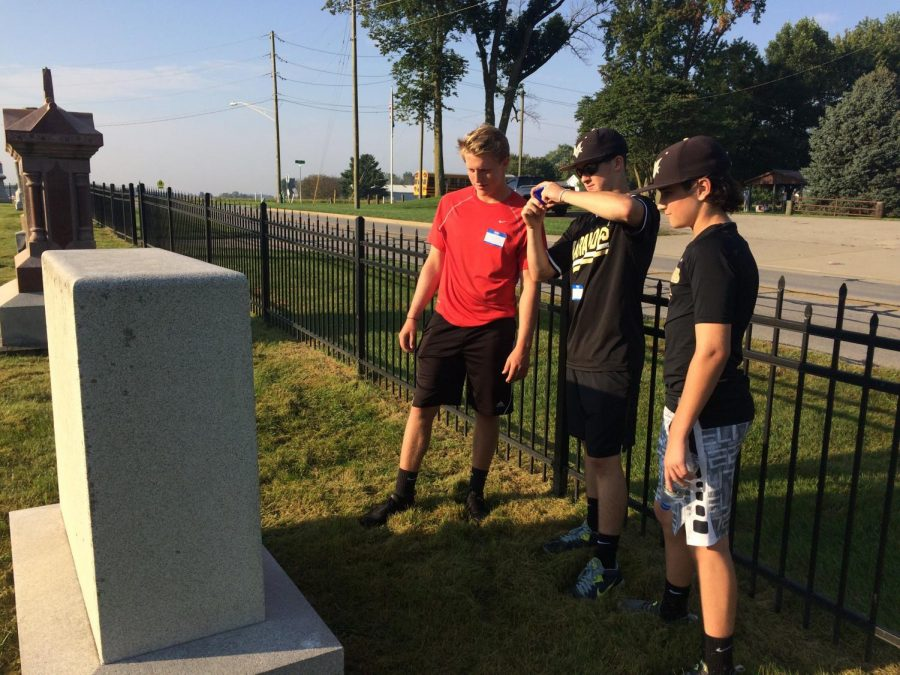 Three male high school students take pictures of local graves while mapping/archiving plots at a local cemetery as part of a service learning project.