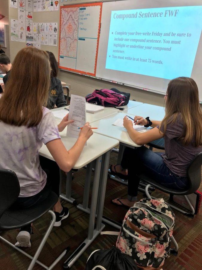 Two freshmen girls work on grammar in their English class.