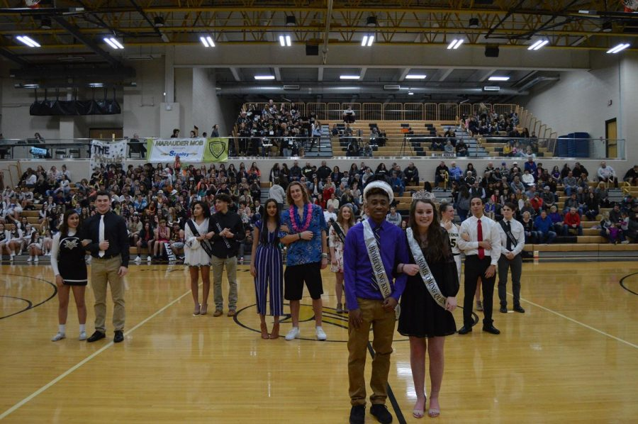 The king and the queen of homecoming are posing for pictures.