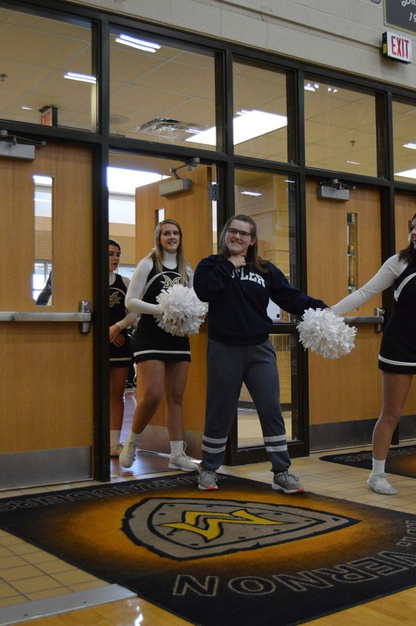 Senior cheerleaders walking in the assembly.