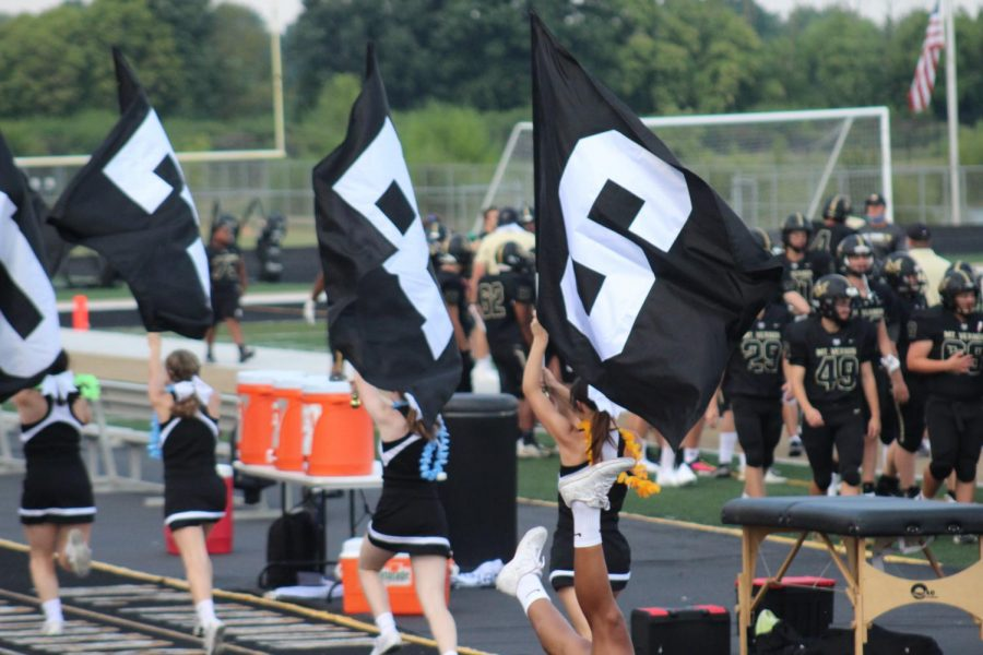 MV Cheerleaders run with flags to celebrate a touchdown